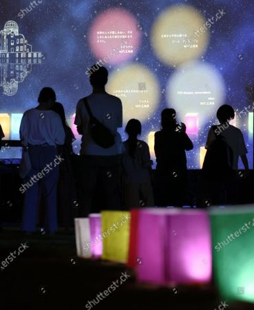 People view a projection of virtual paper lanterns floating in prayer for the victims of the 1945 atomic bombing in Hiroshima, western Japan, 06 August 2020. Japan marks on 06 August 2020 the 75th anniversary of the bombing of Hiroshima. In 1945 the United States dropped two nuclear bombs over the cities of Hiroshima and Nagasaki on 06 and 09 August respectively, killing more than 200,000 people. This year's commemoration events were either canceled or scaled down amid the ongoing coronavirus disease (COVID-19) pandemic.