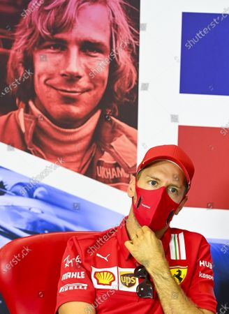 Stock Image of Ferrari driver Sebastian Vettel of Germany, attends the press conference in the build-up to the 70th Anniversary Formula One Grand Prix at the Silverstone circuit, Silverstone, England, . in rear is a portrait of F1 legend James Hunt