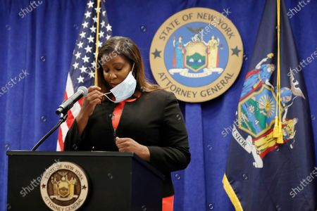 New York State Attorney General Letitia James removes her mask before announcing that the state is suing the National Rifle Association during a press conference, in New York. James said that the state is seeking to put the powerful gun advocacy organization out of business over allegations that high-ranking executives diverted millions of dollars for lavish personal trips, no-show contracts for associates and other questionable expenditures