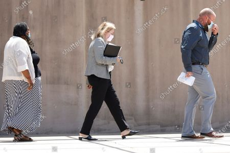 """Aubrey """"Bart"""" Willis, right, and Carolyn Johnson, left, exit the Thad Cochran United States Courthouse in Jackson, Miss., accompanied by their attorney Bethany Johnson, center, after their arraignment in federal court on immigration crimes and other federal charges stemming from the largest single-state worksite enforcement action last year at a number of Mississippi poultry processing plants"""