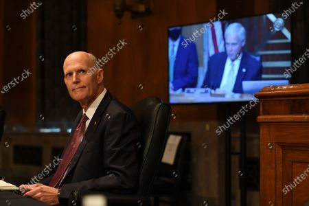 United States Senator Rick Scott (Republican of Florida) listens during the hearing in which acting United States Secretary of Homeland Security Chad F. Wolf, appears before the US Senate Homeland Security and Governmental Affairs Committee in Washington D.C. to explain the use of federal agents during protests in Portland, Oregon. Appearing on the screen at right is US Senator Ron Johnson (Republican of Wisconsin), Chairman, US Senate Committee on Homeland Security and Government Affairs.