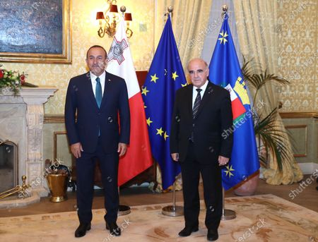 Turkey's Foreign Minister Mevlut Cavusoglu, left, and George Vella, President of the Republic of Malta, pose for photos prior to a meeting, in Valetta, Malta