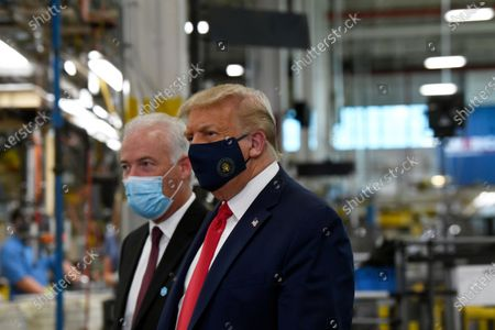 President Donald Trump wears a mask as he gets a tour of the Whirlpool Corporation facility from Jim Keppler, Vice President, Integrated Supply Chain and Quality, Whirlpool Corporation in Clyde, Ohio, . Trump is in Ohio to promote the economic prosperity that much of the nation enjoyed before the coronavirus pandemic and try to make the case that he is best suited to rebuild a crippled economy