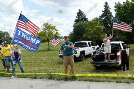 People watch the motorcade of President Donald Trump roll by, before an event at the Whirlpool Corporation in Clyde, Ohio, . Trump is in Ohio to promote the economic prosperity that much of the nation enjoyed before the coronavirus pandemic and try to make the case that he is best suited to rebuild a crippled economy
