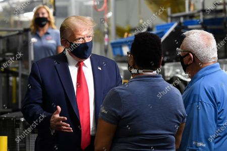 President Donald Trump wears a mask as he talks with employees as he tours the Whirlpool Corporation facility in Clyde, Ohio