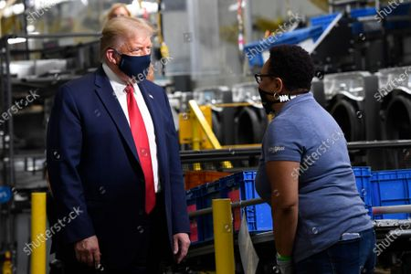 President Donald Trump wears a mask as he talks with an employee as he tours the Whirlpool Corporation facility in Clyde, Ohio