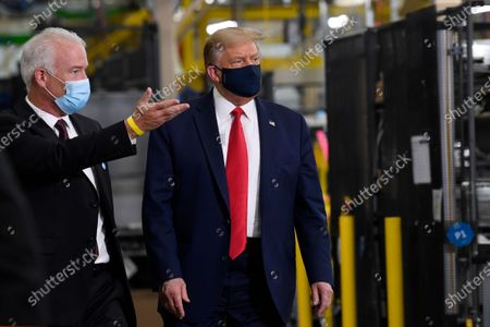 President Donald Trump wears a mask as he gets a tour from Jim Keppler, Whirlpool Corporation Vice President of Integrated Supply Chain and Quality, left, during a tour of the Whirlpool Corporation facility in Clyde, Ohio