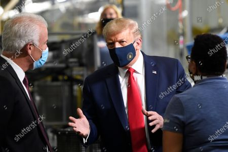 President Donald Trump, center, wears a mask as he talks to Jim Keppler, Whirlpool Corporation Vice President of Integrated Supply Chain and Quality, left, during a tour of the Whirlpool Corporation facility in Clyde, Ohio