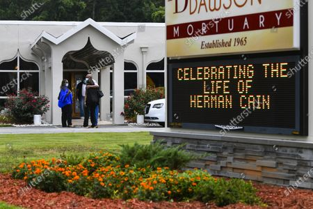 Attendees pause to console each other as they arrive for a private viewing for Herman Cain, in Atlanta. The former Republican presidential candidate, radio host, and entrepreneur died on July 30, after being hospitalized with COVID-19 and will be laid to rest this week. He was 74