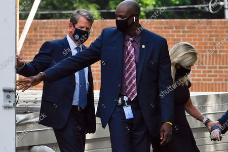 Stock Image of Georgia Gov. Brian Kemp, left, leaves a private viewing for Herman Cain, in Atlanta. Cain, a former Republican presidential candidate, radio host, and entrepreneur died on July 30, after being hospitalized with COVID-19 and will be laid to rest this week. He was 74
