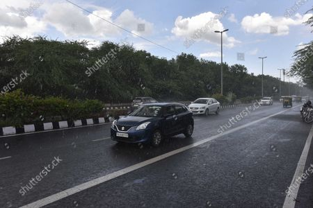 Stock Picture of Commuters out in the rain at Aruna Asif Ali Road on August 6, 2020 in New Delhi, India.