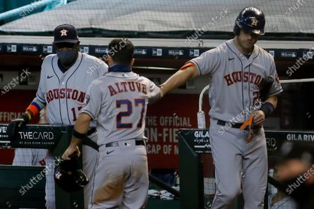 Houston Astros' Jose Altuve (27) is greeted by teammate Josh Reddick and manager Dusty Baker Jr., left, after scoring on a base hit by Yuli Gurriel during the fourth inning of a baseball game against the Arizona Diamondbacks, in Phoenix