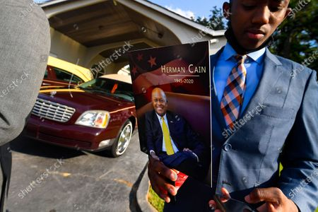 An attendee stands outside a public viewing for Herman Cain, in Atlanta. The former Republican presidential candidate, radio host, and entrepreneur died on July 30 after being hospitalized with-covid-19 and will be laid to rest this week. He was 74