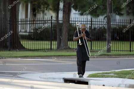 Larry Walker walks along a north Jackson, Miss., street playing his trombone . Walker, who has been playing the instrument since junior high school, says he plays whenever he can