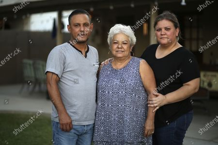"""Rosa Sandoval, center, stands with her son Carlos, left, and daughter Azalia at her home in Phoenix. Rosa said her husband held her face in his hands each time he entered the hospital and said the same thing: """"You are so pretty, I love you so much!"""" The last time Rosa Sandoval heard those words was in mid-June when her husband, Carlos Manuel Sandoval, died after nearly two weeks later from COVID-19 related complications"""