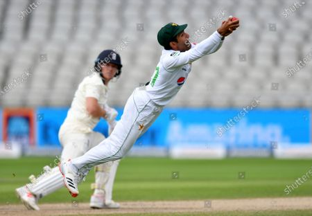 Pakistan's Asad Shafiq, right, dives to catch the ball to dismiss England's Dominic Bess, left, during the third day of the first cricket Test match between England and Pakistan at Old Trafford in Manchester, England