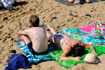 Visitors flock West Bay beach in Dorset as the Met Office issues an amber health warning for what could be the hottest day of the year.