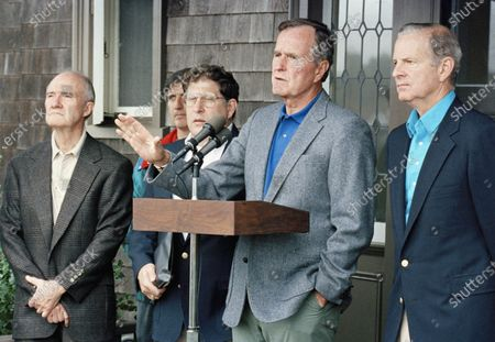 President George H. W. Bush comments to reporters at his Kennebunkport home in Maine, after meeting with his advisers on the Middle East crisis. Listening from left, are National Security Adviser Brent Scowcroft, White House Andy Card (partially hidden), Chief of Staff John Sununu, and Secretary of State James Baker III. A longtime adviser to Presidents Gerald Ford and George H.W. Bush has died. Brent Scowcroft was 95. A spokesperson for the late President Bush says Scowcroft died Thursday of natural causes at his home in Falls Church, Virginia