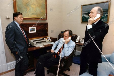 In this file photo, United States President George H.W. Bush speaks with US Secretary of State James A. Baker, III, from his study in the Oval Office of the White House in Washington, DC. Pictured from left to right: White House Chief of Staff John Sununu, the President, and National Security Advisor Brent Scowcroft. Mandatory