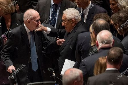 In this file photo, Former National Security advisor for President George H.W. Bush Brent Scowcroft, left, and former Secretary of State Henry Kissinger, center, speak together following the State Funeral for former President George H.W. Bush at the National Cathedral,, in Washington.