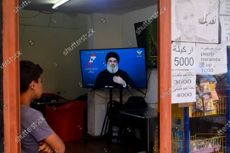 A Lebanese boy listens to Hezbollah leader Hassan Nasrallah on a TV screen three days after explosions that hit Beirut port, in Beirut, Lebanon, 07 August 2020. According to Lebanese Health Ministry, at least 154 people were killed, and more than 5,000 injured in the Beirut blast that devastated the port area on 04 August and believed to have been caused by an estimated 2,750 tons of ammonium nitrate stored in a warehouse.