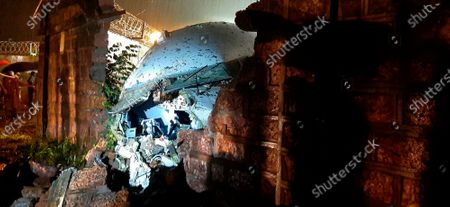 Stock Picture of Part of the Air India Express flight is seen through a broken wall after it skidded off a runway while landing at the airport in Kozhikode, Kerala state, India