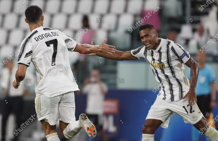 Juventus' Cristiano Ronaldo, left, celebrates with his teammate Alex Sandro, after scoring his side's second goal during the Champions League round of 16 second leg, soccer match between Juventus and Lyon at the Allianz stadium in Turin, Italy