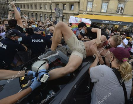 An activist climbs onto a police car to protest the detention of an LGBT activist in Warsaw, Poland, . The incident comes amid rising tensions in Poland between LGBT activists and a conservative government that is opposed to LGBT rights
