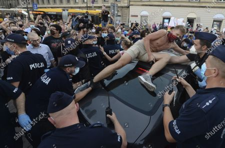 Stock Image of An activist climbs onto a police car to protest the detention of an LGBT activist in Warsaw, Poland, on . The incident comes amid rising tensions in Poland between LGBT activists and a conservative government that is opposed to LGBT rights
