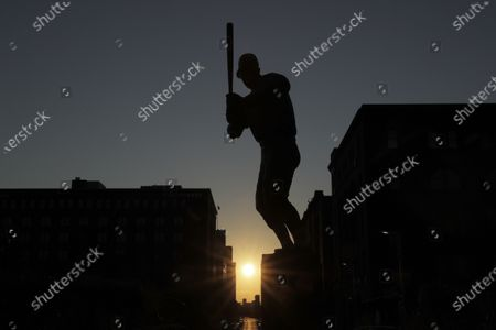 The sun sets in the distance as a statue of St. Louis Cardinals great Stan Musial stands outside a quiet Busch Stadium, in St. Louis. Major League Baseball announced Friday that a three-game series between the Chicago Cubs and Cardinals set for this weekend in St. Louis has been postponed after two more Cardinals players and a staff member tested positive for the coronavirus