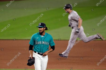 Seattle Mariners relief pitcher Yohan Ramirez, left, waits for another batter as Colorado Rockies' Daniel Murphy rounds the bases behind on Murphy's two-run home run in the eighth inning of a baseball game, in Seattle