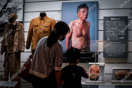 A young boy and his mother look at a portrait of atomic bombing victim Senji Yamaguchi who suffered flash burns, at the Nagasaki Atomic Bomb Museum in Nagasaki, southern Japan, 08 August 2020. Nagasaki is preparing to mark the 75th anniversary of the atomic bombing on 09 August as related events are either canceled or scaled down this year to avoid the spreading of the coronavirus and COVID-19 disease pandemic. In 1945 the United States dropped two nuclear bombs over the cities of Hiroshima and Nagasaki on 06 and 09 August respectively, killing more than 200,000 people.