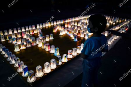 A young boy looks at hundreds of lanterns with messages of peace displayed at the Peace Park in Nagasaki, southern Japan, 08 August 2020. Nagasaki is preparing to mark the 75th anniversary of the 1945 atomic bombing on 09 August as related events are either canceled or scaled down this year to avoid the spreading of the coronavirus disease (COVID-19) pandemic. In 1945 the United States dropped two nuclear bombs over the cities of Hiroshima and Nagasaki on 06 and 09 August respectively, killing more than 200,000 people.