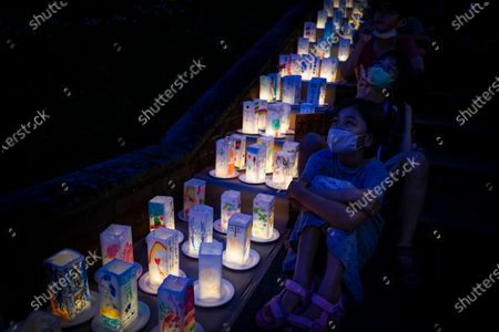 Children pose for a photograph next to hundreds of lanterns with messages of peace at the Peace Park in Nagasaki, southern Japan, 08 August 2020. Nagasaki is preparing to mark the 75th anniversary of the 1945 atomic bombing on 09 August as related events are either canceled or scaled down this year to avoid the spreading of the coronavirus disease (COVID-19) pandemic. In 1945 the United States dropped two nuclear bombs over the cities of Hiroshima and Nagasaki on 06 and 09 August respectively, killing more than 200,000 people.