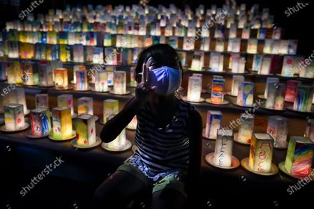 A young girl poses as her mother (out of frame) takes a photo in front of hundreds of lanterns with messages of peace at the Peace Park in Nagasaki, southern Japan, 08 August 2020. Nagasaki is preparing to mark the 75th anniversary of the 1945 atomic bombing on 09 August as related events are either canceled or scaled down this year to avoid the spreading of the coronavirus disease (COVID-19) pandemic. In 1945 the United States dropped two nuclear bombs over the cities of Hiroshima and Nagasaki on 06 and 09 August respectively, killing more than 200,000 people.