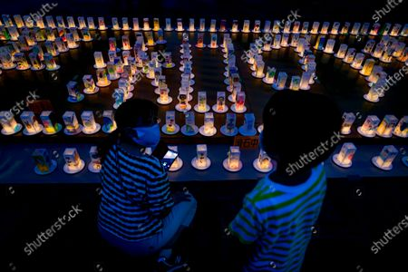 A young boy with his mother looks at hundreds of lanterns with messages of peace at the Peace Park in Nagasaki, southern Japan, 08 August 2020. Nagasaki is preparing to mark the 75th anniversary of the 1945 atomic bombing on 09 August as related events are either canceled or scaled down this year to avoid the spreading of the coronavirus disease (COVID-19) pandemic. In 1945 the United States dropped two nuclear bombs over the cities of Hiroshima and Nagasaki on 06 and 09 August respectively, killing more than 200,000 people.