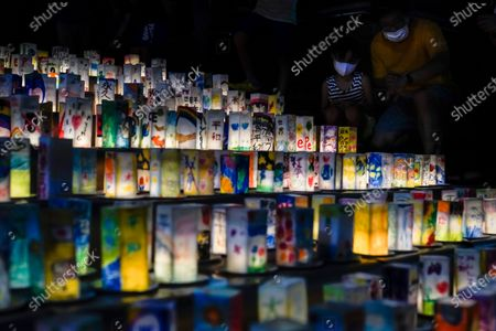 Stock Image of People look at hundreds of lanterns with messages of peace at the Peace Park in Nagasaki, southern Japan, 08 August 2020. Nagasaki is preparing to mark the 75th anniversary of the 1945 atomic bombing on 09 August as related events are either canceled or scaled down this year to avoid the spreading of the coronavirus disease (COVID-19) pandemic. In 1945 the United States dropped two nuclear bombs over the cities of Hiroshima and Nagasaki on 06 and 09 August respectively, killing more than 200,000 people.