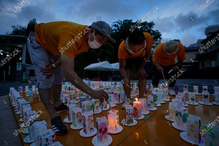 Volunteers light lanterns with a message of peace at the Peace Park in Nagasaki, southern Japan, 08 August 2020. Nagasaki is preparing to mark the 75th anniversary of the 1945 atomic bombing on 09 August as related events are either canceled or scaled down this year to avoid the spreading of the coronavirus disease (COVID-19) pandemic. In 1945 the United States dropped two nuclear bombs over the cities of Hiroshima and Nagasaki on 06 and 09 August respectively, killing more than 200,000 people.