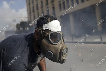 An anti-government protester clashes with riot police officers during a protest against the political elites and the government after this week's deadly explosion at Beirut port which devastated large parts of the capital in Beirut, Lebanon