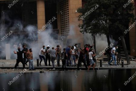 Anti-government protesters clash with riot police officers during a protest against the political elites and the government after this week's deadly explosion at Beirut port which devastated large parts of the capital in Beirut, Lebanon