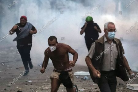 Protestor run away from tear gas during clashes with police as part of a protest against the political elites and the government after this week's deadly explosion at Beirut port which devastated large parts of the capital in Beirut, Lebanon