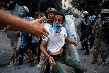 Protestor is evacuated from clashes during a protest against the political elites and the government after this week's deadly explosion at Beirut port which devastated large parts of the capital in Beirut, Lebanon