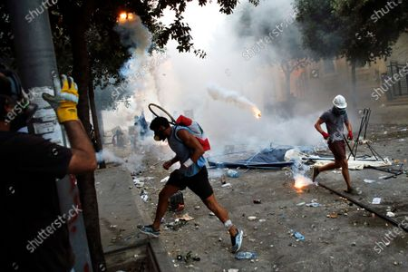 Protesters run away a tear gas canister during clashes with police as part of a protest against the political elites and the government after this week's deadly explosion at Beirut port which devastated large parts of the capital in Beirut, Lebanon