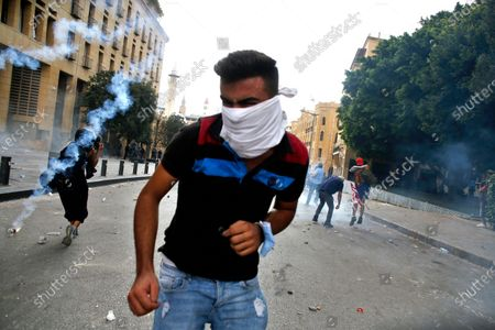 Protester runs away from a tear gas canister during clashes with police as part of a protest against the political elites and the government after this week's deadly explosion at Beirut port which devastated large parts of the capital in Beirut, Lebanon