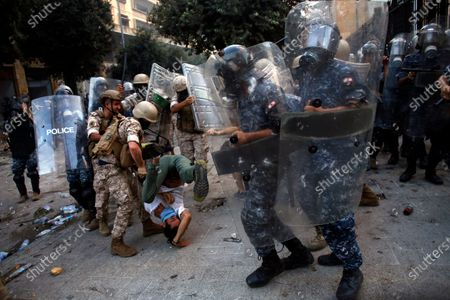 Protester is throw down during clashes with police and Lebanese soldiers as part of a protest against the political elites and the government after this week's deadly explosion at Beirut port which devastated large parts of the capital in Beirut, Lebanon