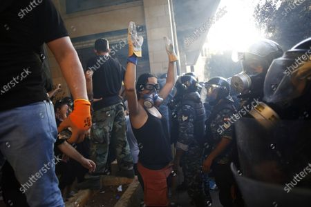 Protestor rises her arms as she faces police during a protest against the political elites and the government after this week's deadly explosion at Beirut port which devastated large parts of the capital in Beirut, Lebanon