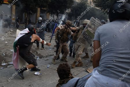 Protestor hits a Lebanese soldier with a baseball bat during clashes with police as part of a protest against the political elites and the government after this week's deadly explosion at Beirut port which devastated large parts of the capital in Beirut, Lebanon