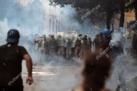 Lebanese soldiers stand among tear gas during clashes with protestors as part of a protest against the political elites and the government after this week's deadly explosion at Beirut port which devastated large parts of the capital in Beirut, Lebanon