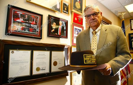 Standing next to his presidential pardon from President Donald Trump, former Arizona Maricopa County Sheriff Joe Arpaio poses for a photograph as he announces his 2020 campaign for Maricopa County Sheriff in Fountain Hills, Ariz. Arpaio's primary defeat in his bid to win back the sheriff's post in metro Phoenix marks what's likely to be the 88-year-old's last political campaign