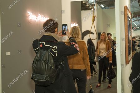 Visitors attend Armory Show Lia Rumma Gallery presentation work by artists Michelangelo Pistoletto & Joseph Kosuth at Piers 92 & 94